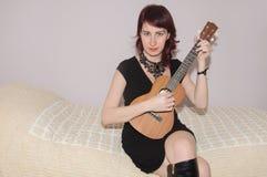 Härlig flicka som spelar ukulelet royaltyfria bilder