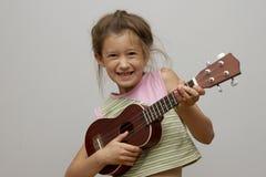 Härlig flicka som spelar ukulelet Arkivfoto