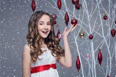 Härlig flicka som står det near trädet med julgarneringar arkivfoto