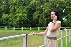 Härlig flicka som talar över mobiltelefonen Fotografering för Bildbyråer