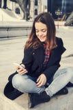 Härlig flicka som talar på mobiltelefonen i stads- stad Arkivbilder
