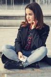 Härlig flicka som talar på mobiltelefonen i stads- stad Royaltyfri Foto
