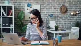 Härlig flicka som talar på mobiltelefonen och skriver på bärbara datorn i modernt kontor lager videofilmer