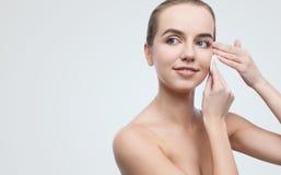 Härlig flicka som tar bort makeup från hennes framsida med bomullsblocket arkivbilder
