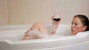 Härlig flicka som tar en bubbelbad med ett exponeringsglas av vin Ett stor vit bad och glädje på hans framsida wrist för watch fö arkivfilmer