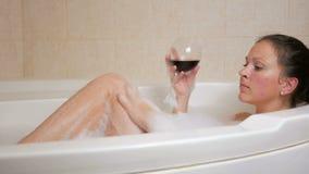 Härlig flicka som tar en bubbelbad med ett exponeringsglas av vin Ett stor vit bad och glädje på hans framsida wrist för watch fö lager videofilmer