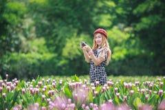 Härlig flicka som tar fotoet vid den mirrorless kameran Fotografering för Bildbyråer