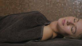 Härlig flicka som tycker om tillvägagångssätten för massage` s i brunnsorten arkivfilmer