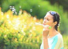 Härlig flicka som utomhus blåser bubblor Arkivbild