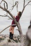 Härlig flicka som utomhus kopplar av i ett träd arkivbilder