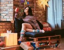 Härlig flicka som värme med en kopp kaffe som tycker om julmorgon, medan sitta på en soffa i ett dekorerat rum arkivbild