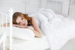Härlig flicka som vaknar upp i vit säng Arkivfoto