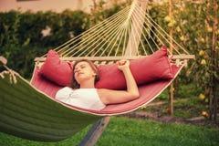 Härlig flicka som vilar i en hängmatta Arkivbild