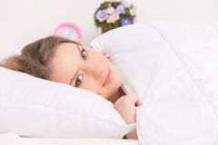 Härlig flicka som vilar på säng och att le Royaltyfria Bilder