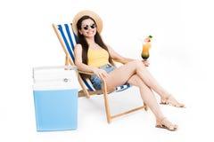 härlig flicka som vilar på strandstol med coctailen och kallare ask, royaltyfri bild