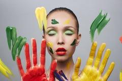 Härlig flicka till och med exponeringsglaset med färgmålarfärg arkivbilder