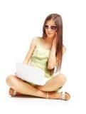 härlig flickabärbar dator genom att använda barn royaltyfria foton