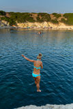 Härlig flickabanhoppning från klippan in i havet royaltyfri fotografi