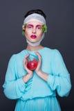 Härlig flickabrunettflicka i blåttmodeklänning med ljust romantiskt smink, blommor på hennes huvud och äpple i händer royaltyfri foto