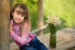 Härlig flickacowboy för gullig fermer i jeans som tycker om sommardag i byliv med blommor som ler happyly Royaltyfri Fotografi