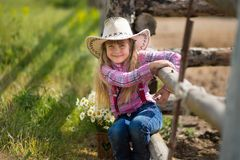 Härlig flickacowboy för gullig fermer i jeans som tycker om sommardag i byliv med blommor som ler happyly Arkivfoton