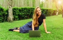 Härlig flickafreelancer på gräset med bärbara datorn arkivbild
