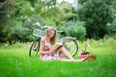 Härlig flickaläsning i en parkera Royaltyfri Foto