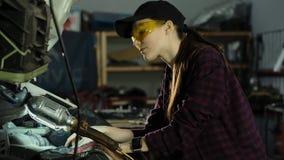Härlig flickamekaniker, brunett, i en plädskjorta och ett lock, i skyddande exponeringsglas som reparerar en bilmotor mot som kro arkivfilmer