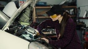 Härlig flickamekaniker, brunett, i en plädskjorta och ett lock, i skyddande exponeringsglas som reparerar en bilmotor mot som kro lager videofilmer