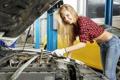 Härlig flickamekaniker som reparerar en bil Arkivbild