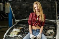 Härlig flickamekaniker som reparerar en bil Arkivbilder