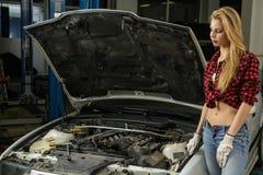 Härlig flickamekaniker som reparerar en bil Royaltyfri Foto