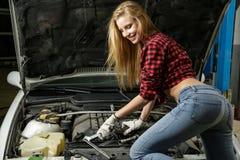 Härlig flickamekaniker som reparerar en bil Royaltyfri Bild