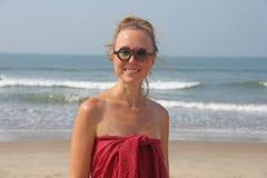 Härlig flickamissfoster i en röd klänning och ett blont hår, på backgen arkivfoton