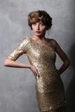 Härlig flickamodell för stående i en guld- klänning Arkivbilder