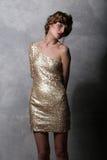 Härlig flickamodell för stående i en lyxig guld- klänning Fotografering för Bildbyråer