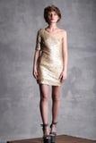 Härlig flickamodell i guld- klänning på full höjd Arkivfoto