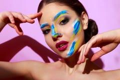 Härlig flickamodemodell med målarfärg på hennes framsida Royaltyfri Bild