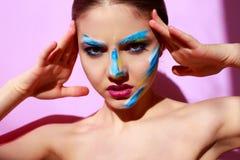 Härlig flickamodemodell med målarfärg på hennes framsida Arkivfoto