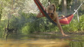 Härlig flickaridning i en hängmatta över vattnet stock video