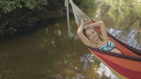 Härlig flickaridning i en hängmatta över vattnet arkivfilmer