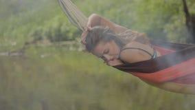 Härlig flickaridning i en hängmatta över vattnet lager videofilmer