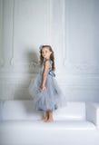 Härlig flickaställning på soffan Royaltyfria Bilder