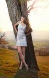 Härlig flickastående med hatten nära ett träd i trädgården. Ung Caucasian sinnlig kvinna i ett romantiskt landskap. Girt i vit Arkivbilder
