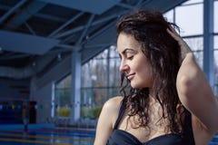 Härlig flickastående nära rörande hår för simbassäng Arkivbilder