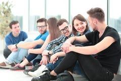 Härlig flickauniversitetsstudent med vänner som sitter på flen Arkivfoto