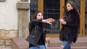 Härlig flickvän två i gatan som talar och dricker kaffe arkivfilmer