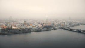 Härlig flyg- cityscapesikt av Riga den gamla staden och bron över floddaugavaen under tjock dimma på molnig höstdag stock video
