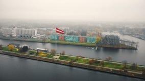 Härlig flyg- cityscapesikt, jätte- flagga av Lettland som vinkar ovanför floddaugavaen, och byggnader på dimmig dag i Riga arkivfilmer
