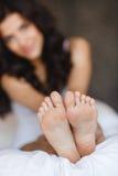 Härlig fot som ligger i sängen av en ung kvinna arkivbilder